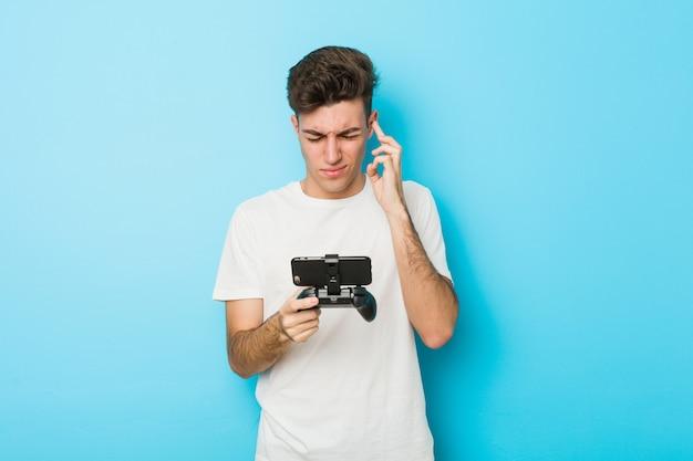 Junger kaukasischer mann, der videospiele mit telefonkreuzfingern spielt, um glück zu haben