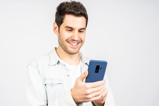 Junger kaukasischer mann, der während der arbeit am mobil gegen eine weiße wand lächelt