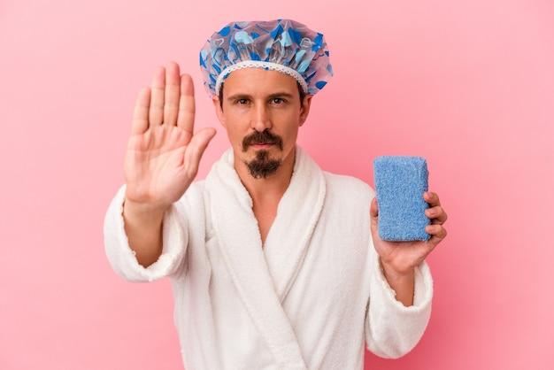 Junger kaukasischer mann, der zur dusche geht, der einen schwamm einzeln auf rosafarbenem hintergrund hält und mit ausgestreckter hand steht und ein stoppschild zeigt, um sie zu verhindern.