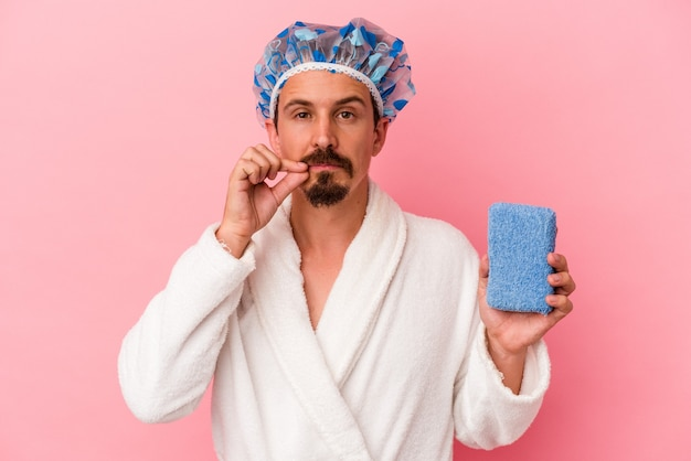 Junger kaukasischer mann, der zur dusche geht und schwamm einzeln auf rosafarbenem hintergrund hält, mit den fingern auf den lippen, die ein geheimnis halten.