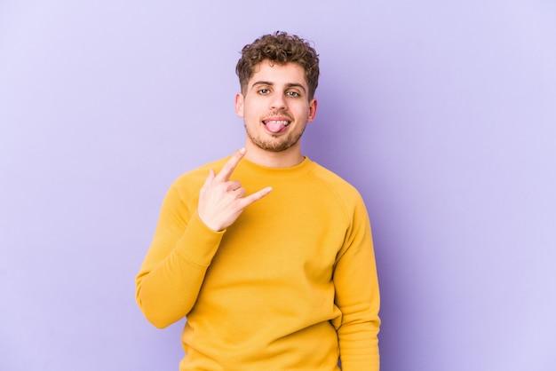 Junger kaukasischer mann des blonden lockigen haares, der felsengeste mit den fingern zeigt
