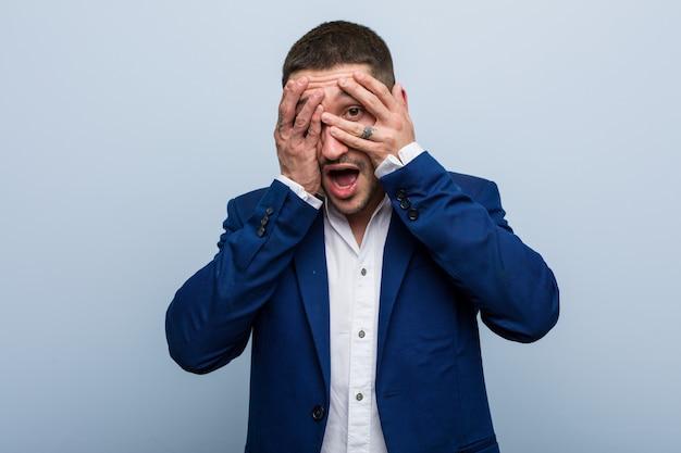 Junger kaukasischer mann des geschäftsblinzelns durch die finger erschrocken und nervös