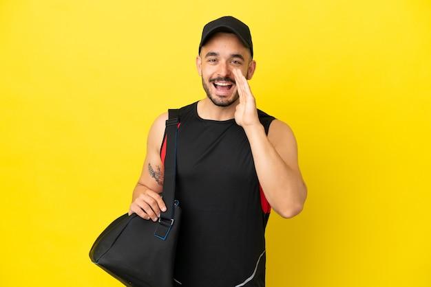 Junger kaukasischer mann des sports mit sporttasche lokalisiert auf gelbem hintergrund, der mit weit geöffnetem mund schreit
