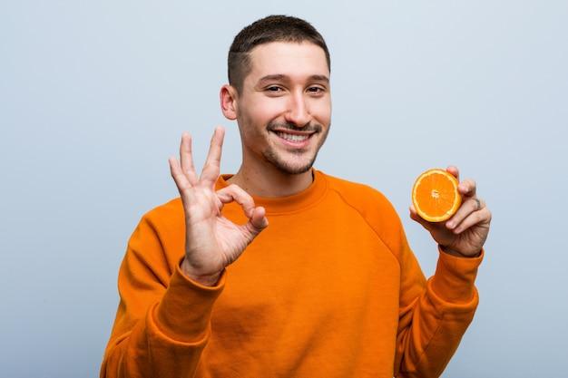 Junger kaukasischer mann eine orange fröhlich und zuversichtlich zeigt ok geste halten.