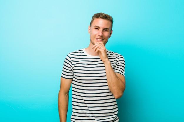Junger kaukasischer mann gegen ein blaues wandlächeln glücklich und überzeugt, rührendes kinn mit der hand.