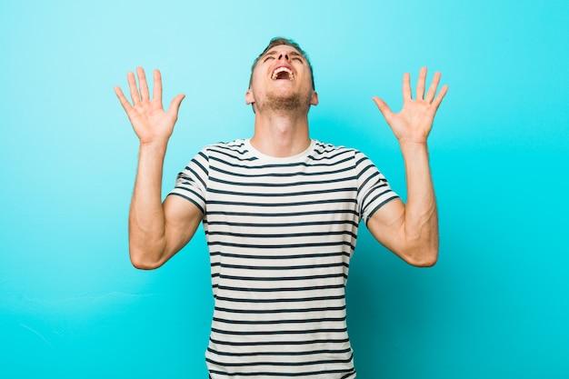 Junger kaukasischer mann gegen eine blaue wand schreiend zum himmel und oben schauen, frustriert.