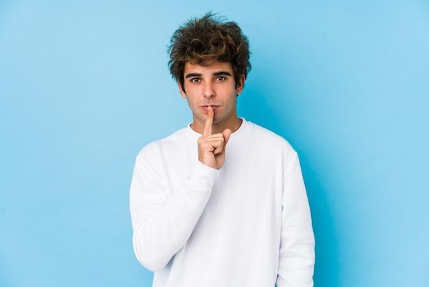 Junger kaukasischer mann gegen eine blaue wand trennte das halten eines geheimnisses oder das bitten um ruhe.