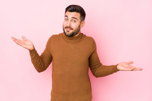Junger kaukasischer mann gegen eine rosa wand, die in fragender geste zweifelt und mit den schultern zuckt.