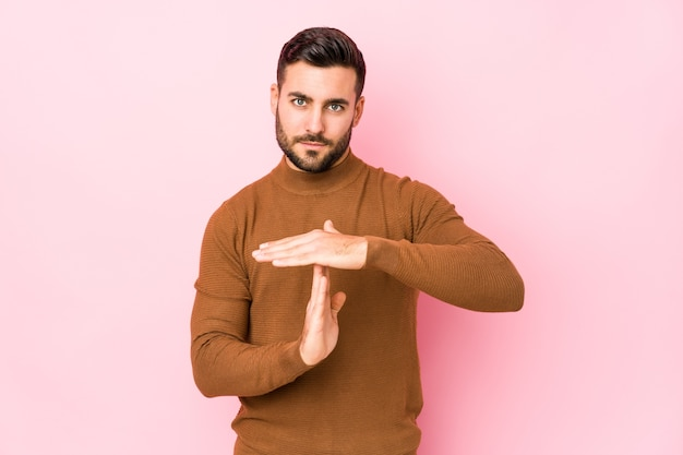 Junger kaukasischer mann gegen eine rosa wand lokalisiert, die eine zeitüberschreitungsgeste zeigt.