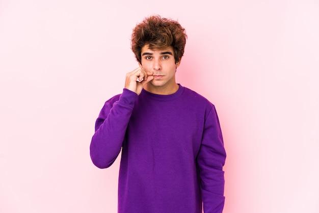 Junger kaukasischer mann gegen eine rosa wand lokalisiert mit den fingern auf den lippen, die ein geheimnis halten.