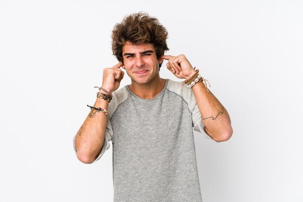 Junger kaukasischer mann gegen eine weiße wand lokalisierte bedeckungsohren mit den händen.