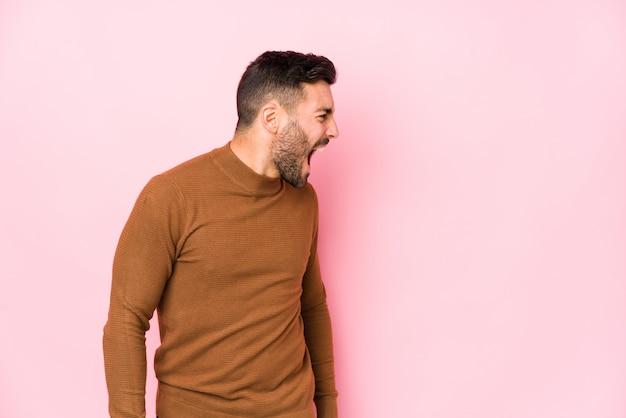 Junger kaukasischer mann gegen einen rosa hintergrund lokalisierte das schreien in richtung eines kopienraums