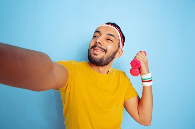 Junger kaukasischer mann im hellen kleidertraining auf blauem raum konzept des sports, der menschlichen gefühle, des gesichtsausdrucks, des gesunden lebensstils, der jugend, des verkaufs