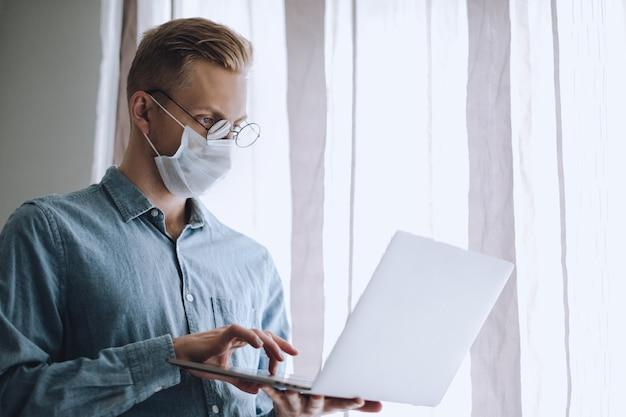 Junger kaukasischer mann in brille und medizinischer schutzmaske arbeitet an einem laptop.