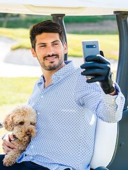 Junger kaukasischer mann in einem golfwagen, der ein selfie mit seinem goldendoodle-welpen auf einem golfplatz macht