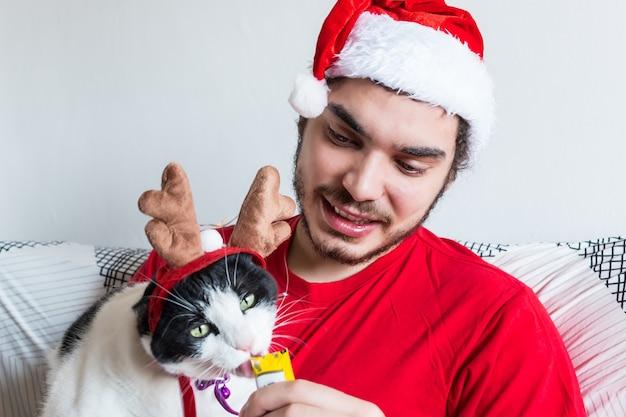 Junger kaukasischer mann in einem weihnachtsmannhut, der seine weiße und schwarze katze in elchhörnern füttert