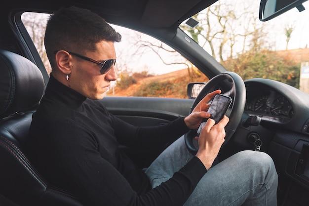 Junger kaukasischer mann innerhalb eines autos unter verwendung eines smartphones
