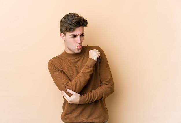 Junger kaukasischer mann isoliert auf beigem hintergrund verwirrt, fühlt sich zweifelhaft und unsicher.