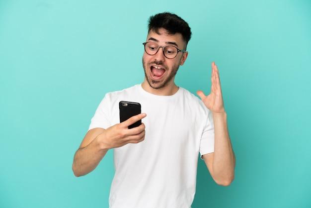 Junger kaukasischer mann isoliert auf blauem hintergrund, der die kamera anschaut, während er das handy mit überraschtem ausdruck benutzt
