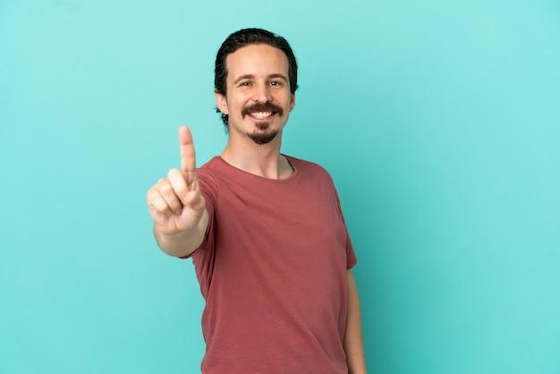 Junger kaukasischer mann isoliert auf blauem hintergrund, der einen finger zeigt und anhebt