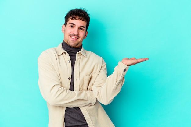 Junger kaukasischer mann isoliert auf blauem hintergrund, der einen kopienraum auf einer handfläche zeigt und eine andere hand an der taille hält.