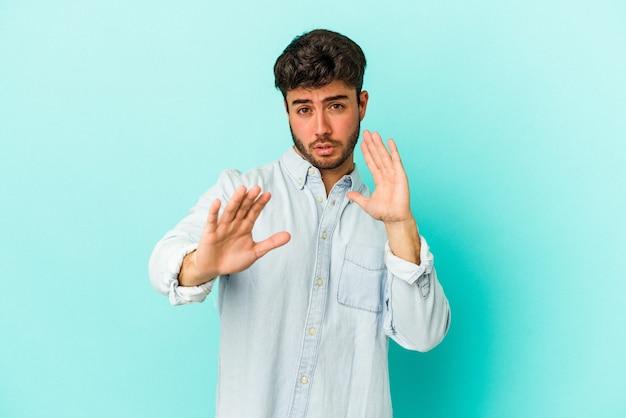 Junger kaukasischer mann isoliert auf blauem hintergrund, der jemanden ablehnt, der eine geste des ekels zeigt.