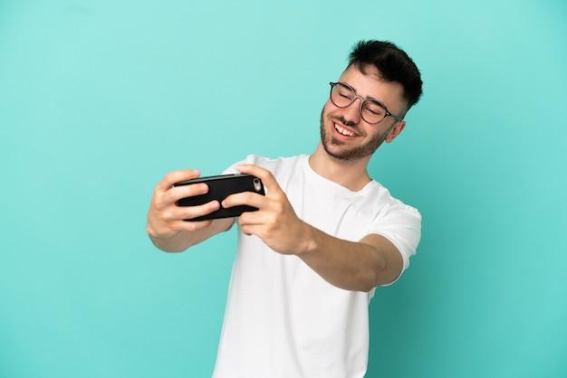 Junger kaukasischer mann isoliert auf blauem hintergrund, der mit dem handy spielt