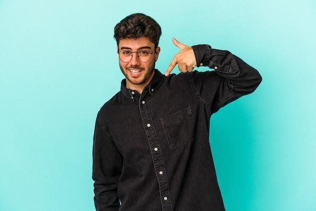 Junger kaukasischer mann isoliert auf blauem hintergrund, der mit der hand auf einen hemdkopierraum zeigt, stolz und selbstbewusst