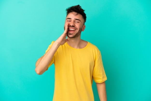 Junger kaukasischer mann isoliert auf blauem hintergrund, der mit weit geöffnetem mund schreit