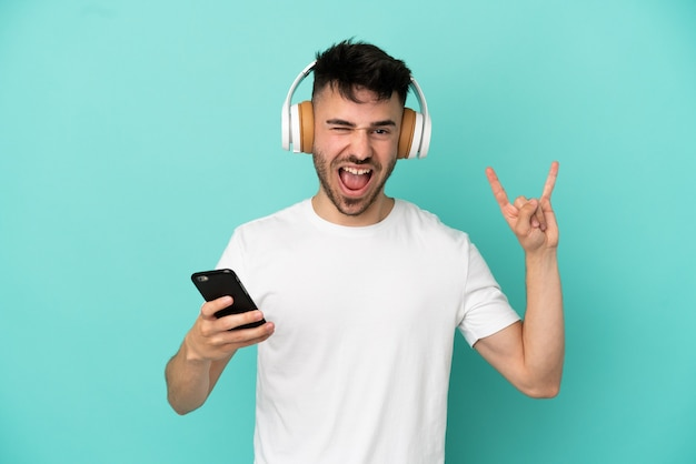 Junger kaukasischer mann isoliert auf blauem hintergrund, der musik mit einem handy hört, das rockgeste macht
