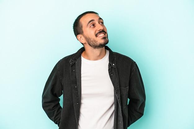 Junger kaukasischer mann isoliert auf blauem hintergrund entspannt und glücklich lachend, hals gestreckt, zähne zeigend.