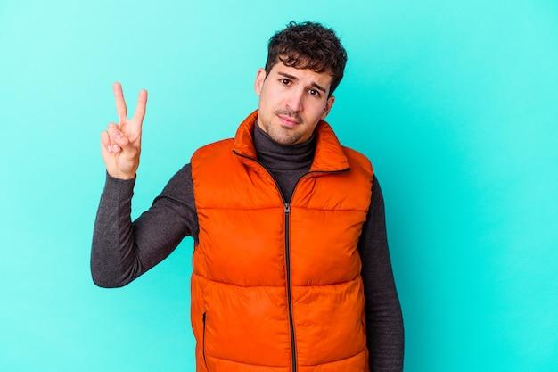 Junger kaukasischer mann isoliert auf blauem hintergrund fröhlich und sorglos, der ein friedenssymbol mit den fingern zeigt.