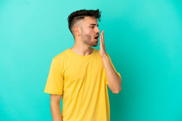 Junger kaukasischer mann isoliert auf blauem hintergrund gähnt und bedeckt weit geöffneten mund mit der hand