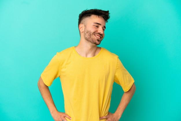 Junger kaukasischer mann isoliert auf blauem hintergrund posiert mit armen an der hüfte und lächelt