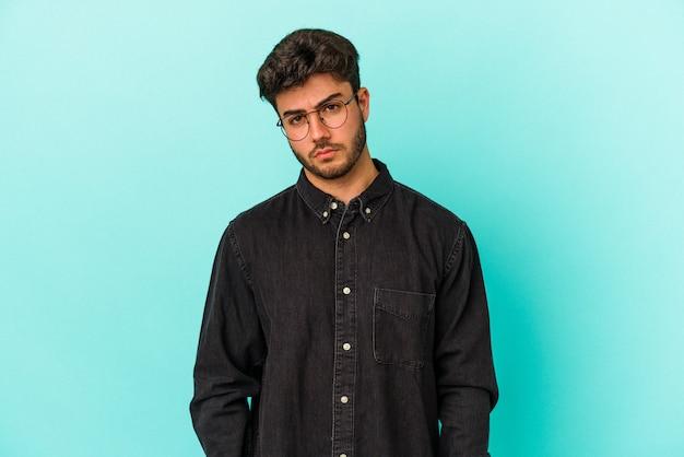 Junger kaukasischer mann isoliert auf blauem hintergrund trauriges, ernstes gesicht, fühlt sich elend und unzufrieden.