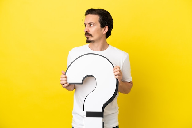 Junger kaukasischer mann isoliert auf gelbem hintergrund, der ein fragezeichen-symbol hält und zur seite schaut