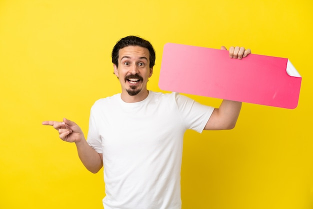 Junger kaukasischer mann isoliert auf gelbem hintergrund, der ein leeres plakat hält und auf die seite zeigt