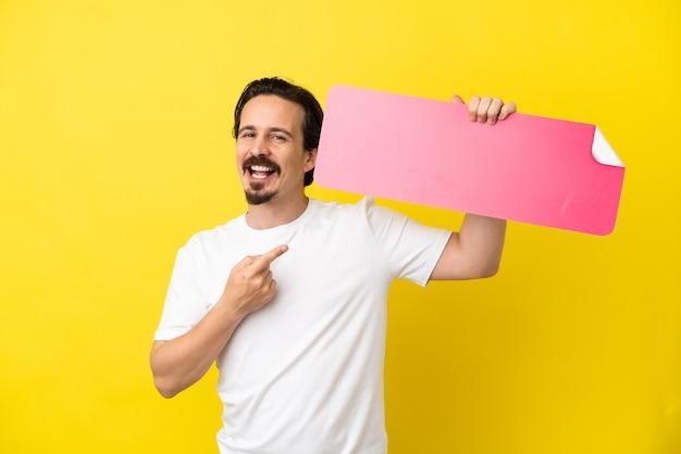 Junger kaukasischer mann isoliert auf gelbem hintergrund, der ein leeres plakat hält und darauf zeigt