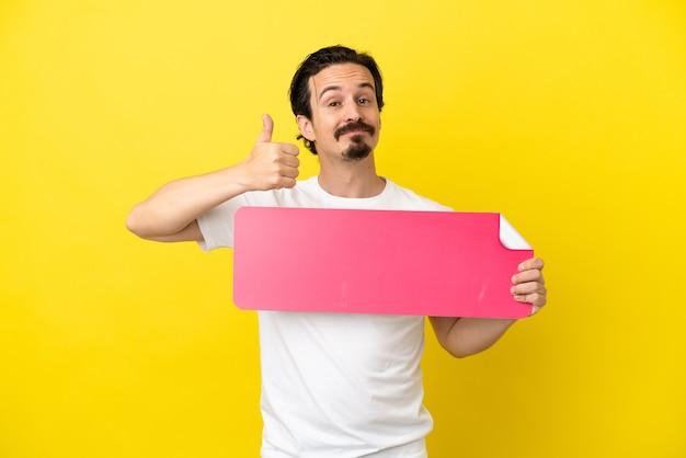 Junger kaukasischer mann isoliert auf gelbem hintergrund, der ein leeres plakat mit dem daumen nach oben hält