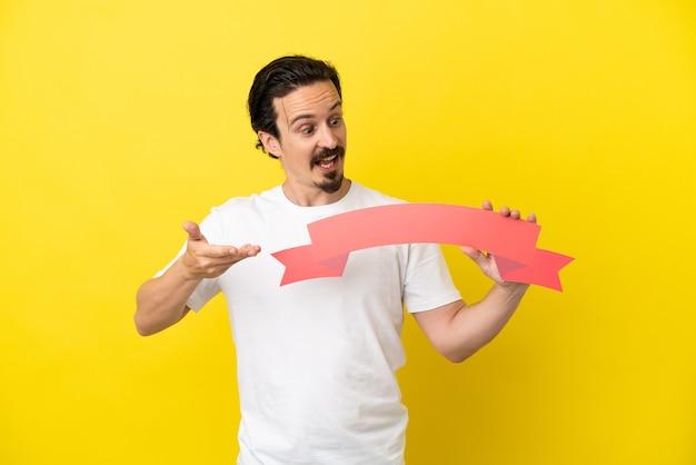 Junger kaukasischer mann isoliert auf gelbem hintergrund, der ein leeres plakat mit überraschtem ausdruck hält