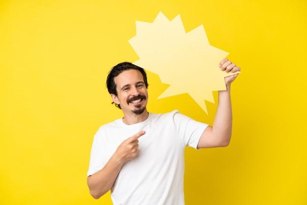 Junger kaukasischer mann isoliert auf gelbem hintergrund, der eine leere sprechblase hält und darauf zeigt