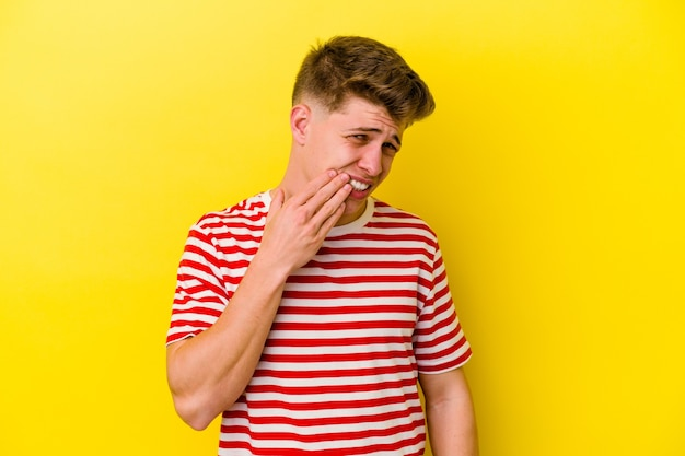 Junger kaukasischer mann isoliert auf gelber wand, die einen starken zahnschmerz, backenzahnschmerz hat.