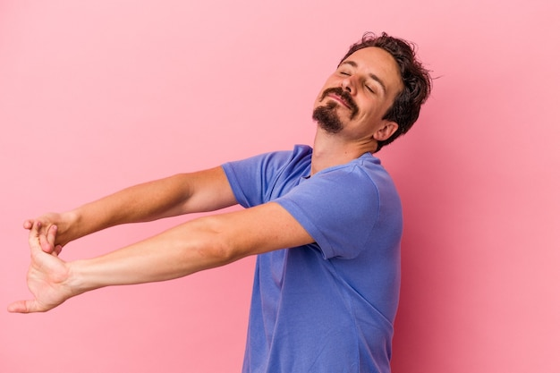 Junger kaukasischer mann isoliert auf rosa hintergrund, der die arme ausdehnt, entspannte position.