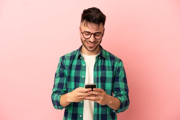 Junger kaukasischer mann isoliert auf rosa hintergrund, der eine nachricht mit dem handy sendet