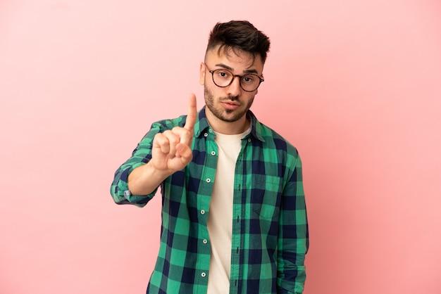 Junger kaukasischer mann isoliert auf rosa hintergrund, der eins mit ernstem ausdruck zählt