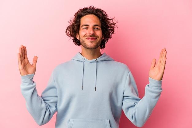 Junger kaukasischer mann isoliert auf rosafarbenem hintergrund, der etwas kleines mit den zeigefingern hält, lächelnd und selbstbewusst.