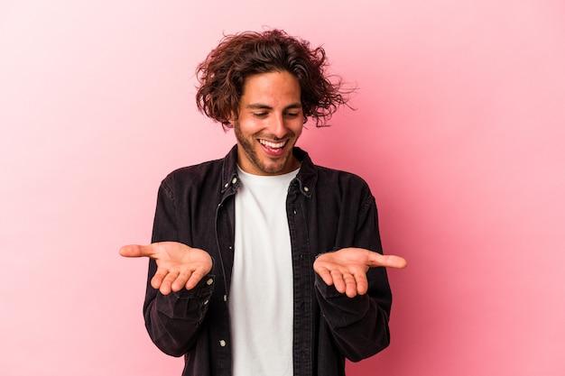 Junger kaukasischer mann isoliert auf rosafarbenem hintergrund, der etwas mit palmen hält und der kamera anbietet.