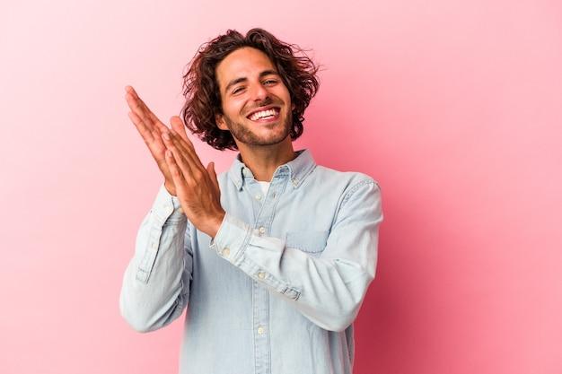 Junger kaukasischer mann isoliert auf rosafarbenem hintergrund, der sich energisch und bequem fühlt und sich die hände selbstbewusst reibt