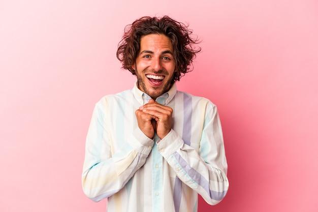 Junger kaukasischer mann isoliert auf rosafarbenem hintergrund, der um glück betet, erstaunt und den mund öffnet, der nach vorne schaut.