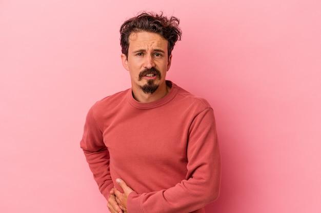 Junger kaukasischer mann isoliert auf rosafarbenem hintergrund mit leberschmerzen, bauchschmerzen.